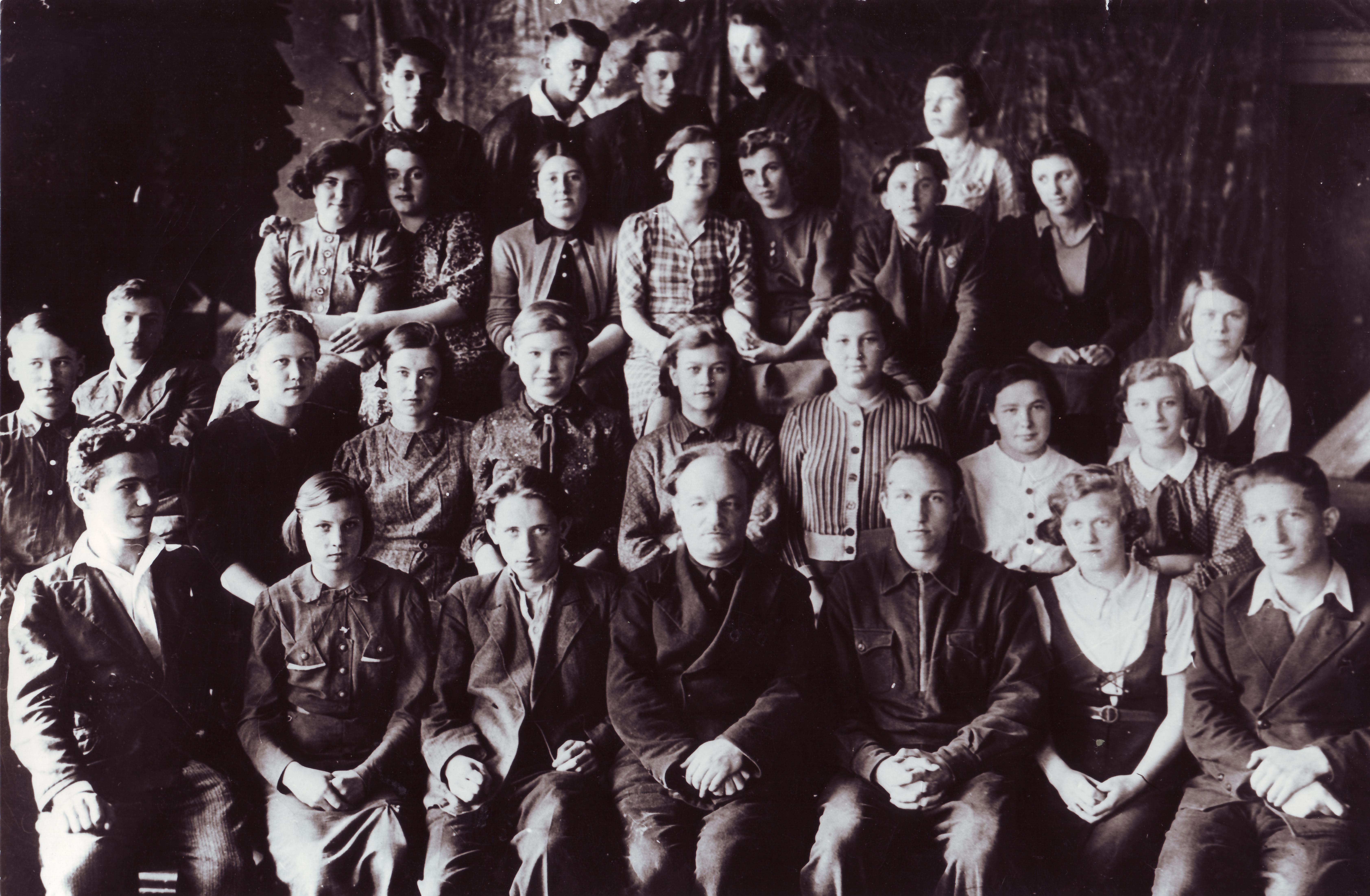"""9 класс """"А"""". 1941 год. Зоя Космодемьянская четвёртая справа во втором ряду (в полосатой кофточке), Саша Космодемьянский крайний слева (сидит вполоборота)."""