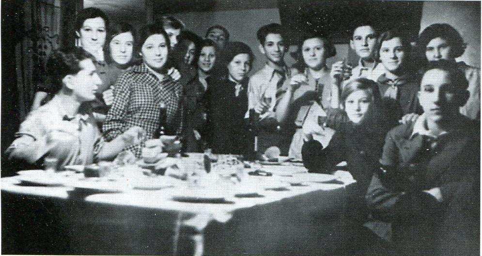 """1939 год. Зоя Космодемьянская крайняя слева (стоит), Саша Космодемьянский крайний справа (сидит). """"Во многих музеях это фото имеет подпись """"На дне рождения Люси Гусевой"""". На самом деле отмечался не день рождения, а 7 (8) ноября. Люся Гусева - дочь директора завода им. Войкова, у их семьи была отдельная квартира, едва ли не у единственной из класса. Поэтому там и собрался 7 """"А"""". Конечно, это ещё были и осенние каникулы. Но главное - праздник. Об этом мне рассказала одноклассница Зои Елизавета Дмитриевна Рябоконь*, она на этой вечеринке была и есть на фото"""". (Из воспоминаний историка Екатерины Ивановой). Вероятно, Е. Д. Рябоконь стоит рядом с Зоей. - прим. адм."""